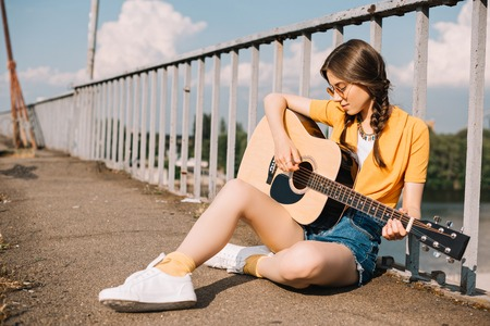 Photo for Young woman with guitar sitting on ground and performing on street - Royalty Free Image