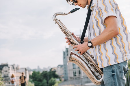 Photo for Young hipster man with saxophone performing on street - Royalty Free Image