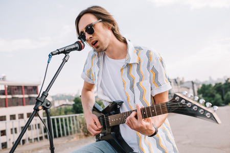 Photo for Young man in sunglasses playing guitar and singing in urban environment - Royalty Free Image