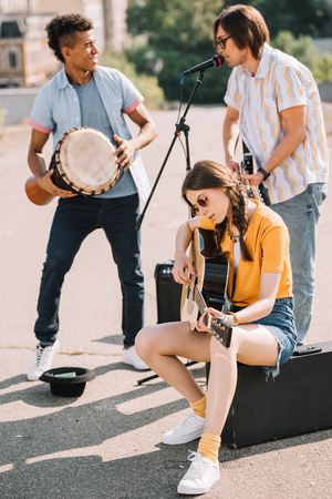Photo for Young and happy multiracial male and female street musicians in city - Royalty Free Image