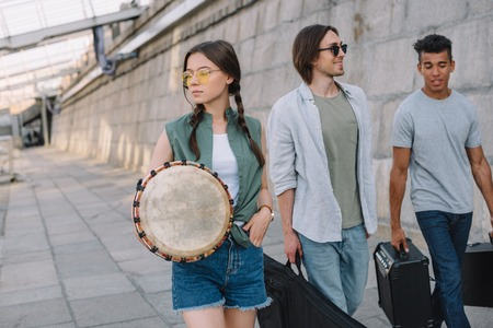 Photo for Team of young male and female friends walking and carrying musical instruments in urban environment - Royalty Free Image