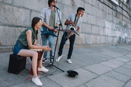 Photo for Young happy woman with drum and men with guitar and djemba at city street - Royalty Free Image