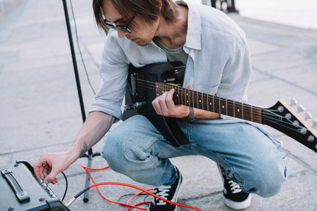Photo for Young man adjusting guitar amplifier while performing on street - Royalty Free Image