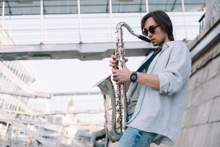 Photo for Young man in sunglasses adjusting saxophone on sunny city street - Royalty Free Image