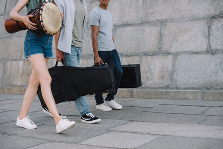 Photo for Cropped view of young people in band walking and carrying musical instruments - Royalty Free Image