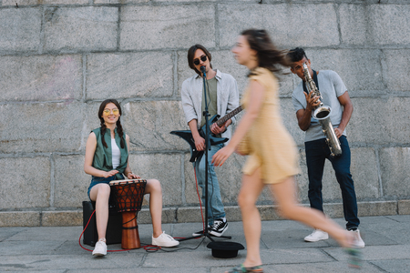 Photo for Woman passing by multiracial band of street musicians in urban environment - Royalty Free Image