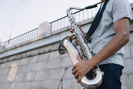 Photo for Cropped view of african american man playing saxophone performing on sunny city street - Royalty Free Image