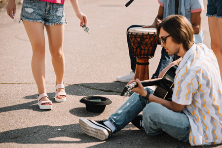 Photo for Young happy buskers playing an improvised concert at city street and receiving money - Royalty Free Image