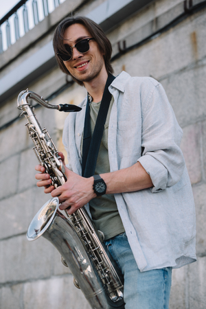 Photo for Smiling hipster man in sunglasses holding saxophone in urban environment - Royalty Free Image