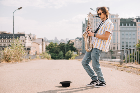 Photo for Young happy male busker playing saxophone at city street - Royalty Free Image