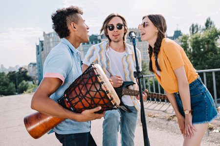 Photo for Team of young friends with musical instruments singing by microphone in urban environment - Royalty Free Image