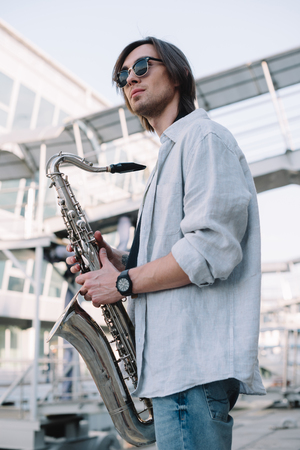 Photo for Stylish guy in sunglasses holding saxophone in city - Royalty Free Image