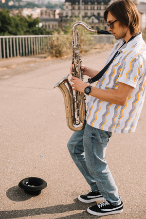 Photo for Young man with saxophone performing in urban environment - Royalty Free Image