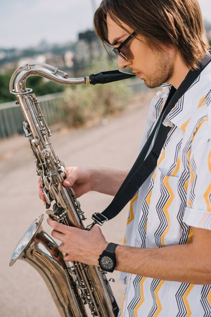 Photo for Young man with saxophone performing on sunny city street - Royalty Free Image