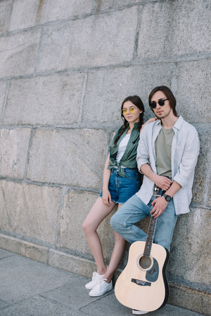 Photo for Young and happy couple in sunglasses with guitar by wall in city - Royalty Free Image