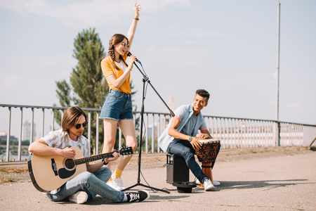 Photo for Multiracial young people performing singing on street - Royalty Free Image