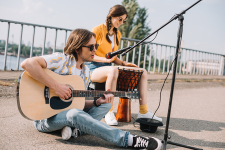 Photo for Young and happy couple street musicians playing in city - Royalty Free Image
