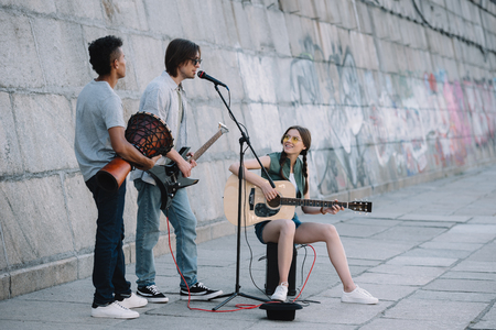 Photo for Team of young friends playing guitars and djembe in urban environment - Royalty Free Image