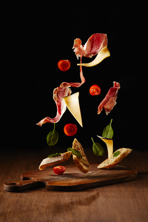 Photo pour Ingredients for snack with bread, jamon and vegetables flying above wooden table surface - image libre de droit