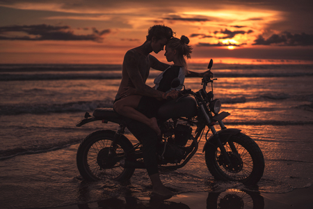 Foto de passionate couple hugging and touching with foreheads on motorcycle at beach during sunset - Imagen libre de derechos