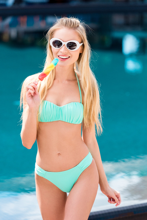 Photo for happy young woman in bikini and vintage sunglasses with colorful popsicle at poolside - Royalty Free Image