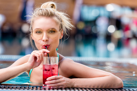 Foto de beautiful young woman drinking fresh cocktail at poolside - Imagen libre de derechos
