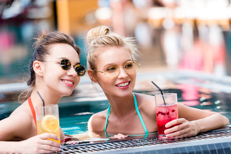 Photo pour beautiful young women with delicious cocktails relaxing in swimming pool and chatting - image libre de droit