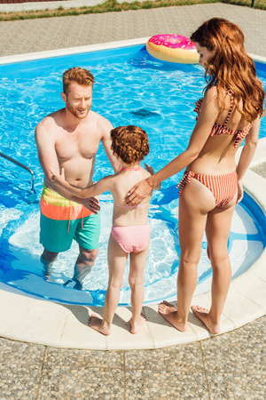 Photo pour beautiful young family spending time together at poolside - image libre de droit