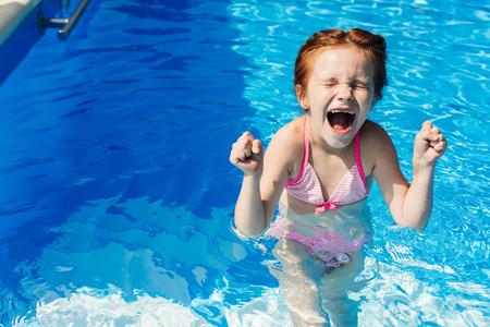 Photo pour screaming little child in bikini in swimming pool - image libre de droit