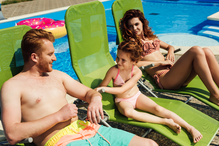 Photo for happy young family relaxing on sun loungers together - Royalty Free Image