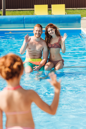 Photo pour rear view of little girl waving to parents at swimming pool - image libre de droit
