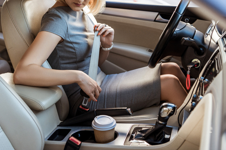 Photo pour cropped image of businesswoman fastening safety belt in car - image libre de droit