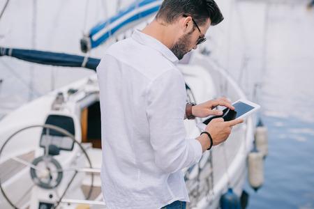 Photo pour back view of man in sunglasses using digital tablet near yacht - image libre de droit