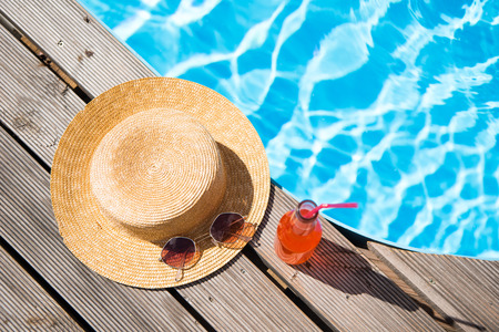 Photo pour top view of wicker hat, sunglasses and bottle with summer drink near swimming pool - image libre de droit