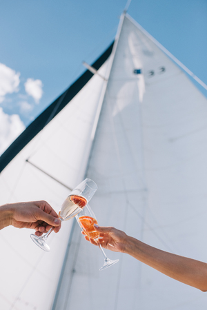 Photo pour cropped image of boyfriend and girlfriend clinking by glasses with champagne on yacht - image libre de droit