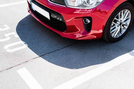 Photo pour Close-up view of red car on street parking lot - image libre de droit