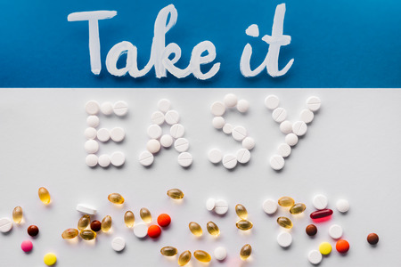 Photo pour top view of lettering take it easy made by pills near various tablets on colorful background - image libre de droit
