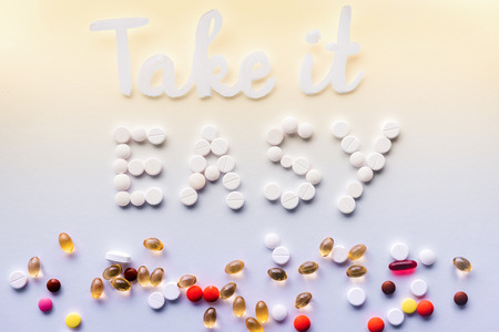 Photo pour top view of lettering take it easy made by white pills near various tablets on colorful background - image libre de droit