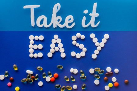 Photo pour top view of lettering take it easy by white pills near various tablets on blue background - image libre de droit
