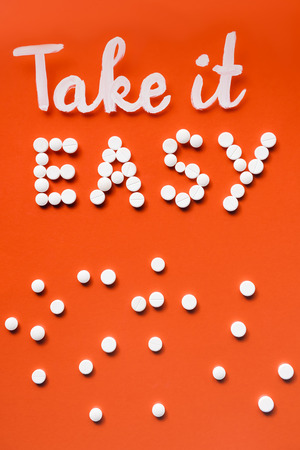 Photo pour top view of lettering take it easy by white pills on red background - image libre de droit