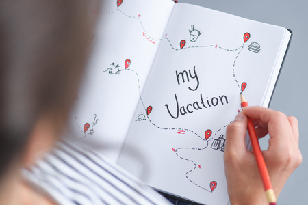 Foto de partial view of woman with pencil holding notebook with my vacation inscription, traveling concept - Imagen libre de derechos