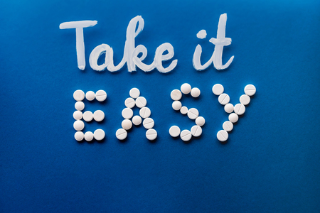 Photo pour top view of lettering take it easy made by white pills on blue background - image libre de droit