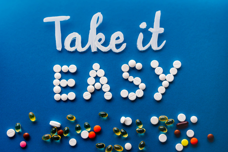 Photo pour top view of lettering take it easy made by white pills near various tablets on blue background - image libre de droit