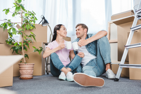 Foto de smiling young couple sitting on floor together and clinking mugs with coffee while moving into new home - Imagen libre de derechos