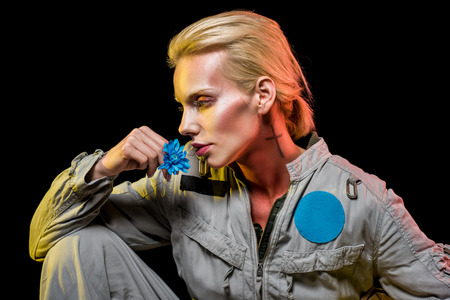 Photo pour beautiful female cosmonaut posing in spacesuit with blue flower, isolated on black - image libre de droit