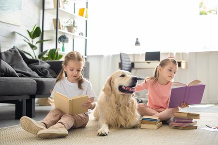 Photo pour cute little sisters reading books with golden retriever dog near by at home - image libre de droit