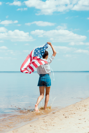 Foto de rear view of young woman running in sea water with american flag, independence day concept - Imagen libre de derechos
