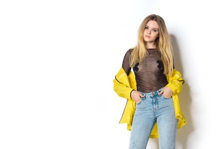 Foto de stylish young woman in transparent shirt and yellow jacket on white - Imagen libre de derechos