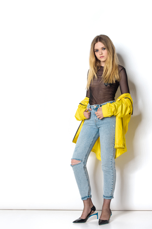 Foto de beautiful young woman in transparent shirt and yellow jacket on white - Imagen libre de derechos