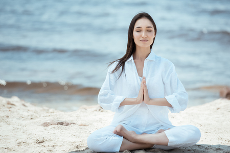 Foto de concentrated young asian woman in anjali mudra (salutation seal) pose on beach - Imagen libre de derechos